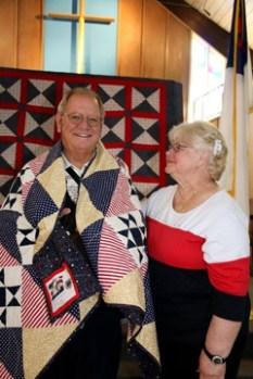 Mrs. Ginger Lewis looks proudly on as her husband Clay, U.S. Air Force Fighter Pilot in Vietnam, 1968, 1972-73, accepts his Quilt of Valor.