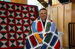 Chaplain Muehler, of the Lutheran Church-Missouri Synod's Office of Ministry to the Armed Forces, is proudly wrapped in his Quilt of Valor, presented by CTK's Sewn to Honor quilting group.