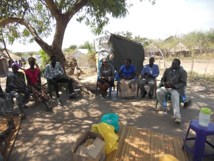 Pastor Bol sitting under a tree with some of Lutheran media ministry before the beginning of women teaching