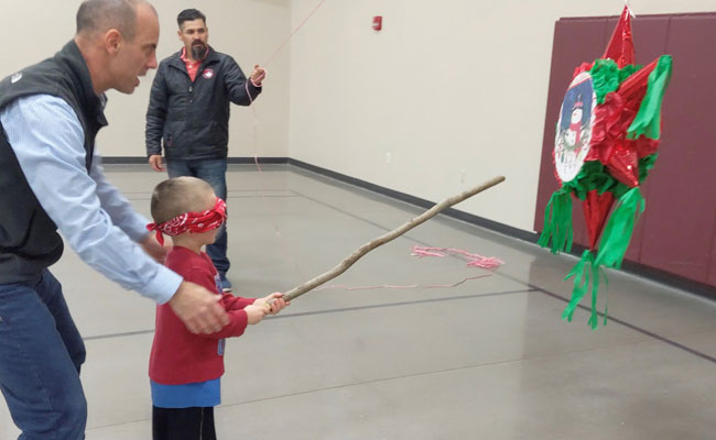 Pastor helping child to hit the pinata