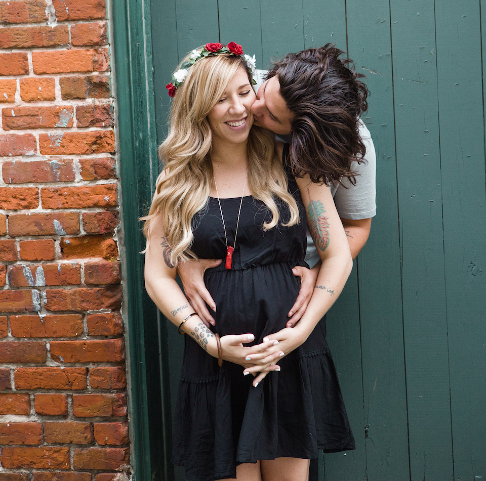 Maternity Photography - Couple Embracing in front of wooden fence and brick wall