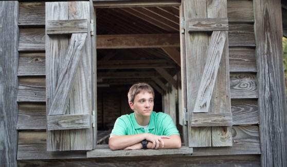 Senior Photography - Senior boy leaning on window seal looking away