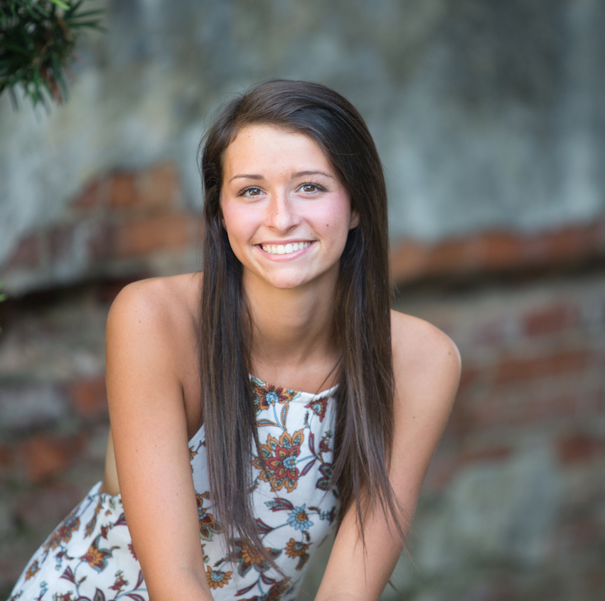 Senior Photography - Senior girl in dress posing in front of brick wall