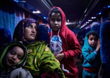 A Malian migrant woman with her children is transferred by bus to a temporary shelter upon their arrival in Bamako after being repatriated from Libya by IOM/AFP
