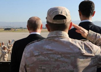 Russian President Vladimir Putin and Syrian President Bashar Assad watch troops marching at the Hemeimeem air base in Syria AP