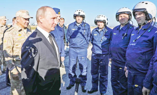 Valdimir Putin and Defence Minister Sergei Shoigu meet Russian air force pilot during their visit to the Russian air base in Syria./AFP