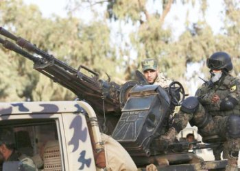 members of libyan pro-government forces ride an army vehicle in bengazi/ REUTERS
