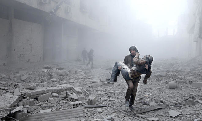 A wounded man is carried following an airstrike on the opposition- held besieged town of Arbin, in the eastren Ghouta region on the outskirts of the capital Damascus on Tuesday/AFP