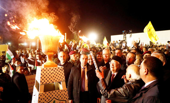 Palestinian President Mahmoud Abbas lights a torch during sunday's rally in Ramallah , marking the 53rd anniversay of the founding of the Fatah movement/REUTERS