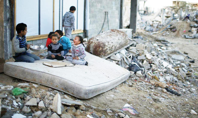 Palestinian children paly on a mattress near the ruins of house which witnesses said were destroyed by Israeli shelling in Gaza in 2014/REUTERS