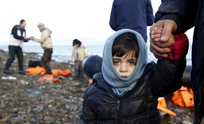 A Syrian refugee child looks on, moments after arriving on a raft with other Syrian refugee on a beach on the Greek island of Lesbos, January 4,2016/REUTERS