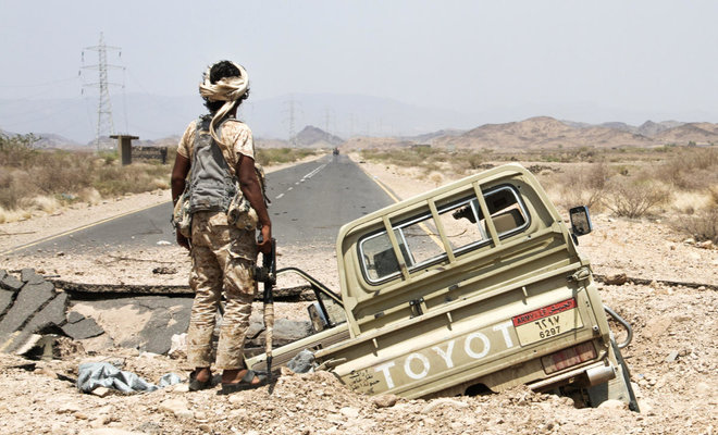 A Yemeni fighter loyal to the Saudi-backed Yemeni presidet stands next t an army Toyota pickup truck as it lies in hole on the road. /AFP
