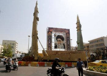 Iranians walk past Sejjil (L) and Qadr-H medium range ballistic missiles displayed next to a portrait of Iranian Supreme Leader Ayatollah Ali Khamenei (AFP)