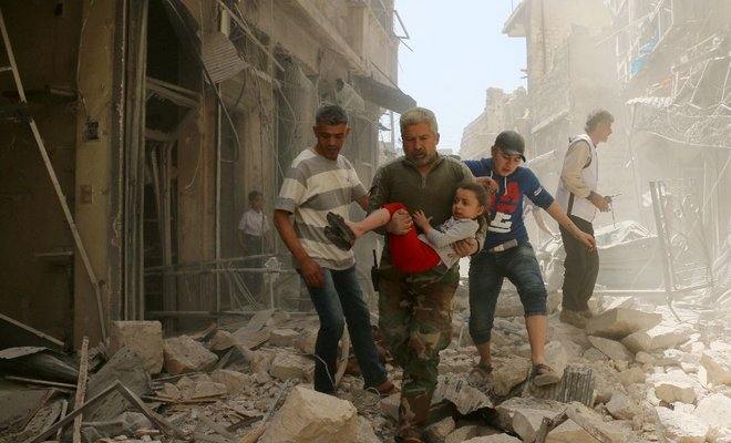 A Syrian man carries a child as they evacuate an area following a reported airstrike on April 22, 2016 in Syria's second city Aleppo. (AFP)