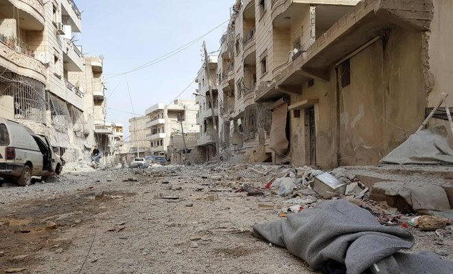 A picture taken on March 19, 2018 shows a body covered with a blanket in a street in the Syrian Kurdish city of Afrin a day after Turkish-led forces entered the city. (AFP)