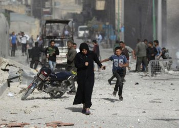 A woman runs after an airstrike in Idlib, Syria. (Reuters)
