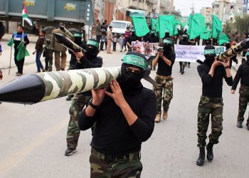 Palestinian militants from the Ezzedine al-Qassam brigade, the armed wing of Hamas, carry mock-rockets as they march during a rally to commemorate the 27th anniversary of the Islamist movement's creation, at the Nuseirat refugee camp in the Central Gaza Strip, in this file photo taken on December 12, 2014. (AFP)