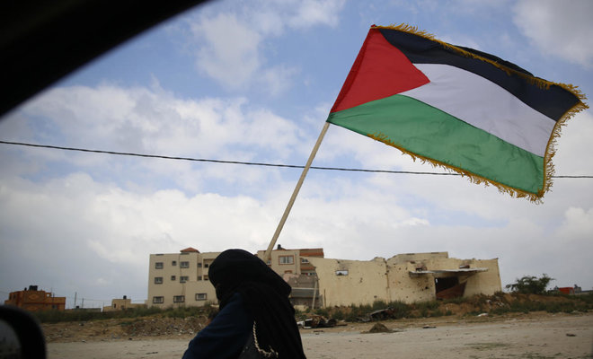 A Palestinian woman holds a Palestinian flag during a demonstration near the Gaza Strip border with Israel, in eastern Gaza City, Friday, March 30, 2018. (AP)