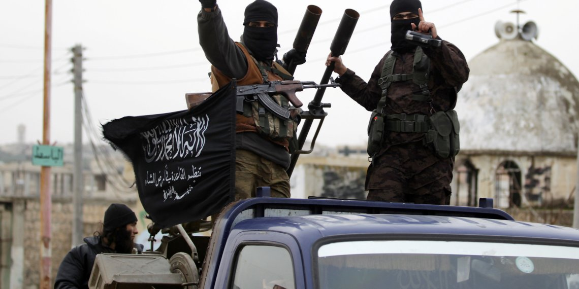 FILE PHOTO: Members of al Qaeda's Nusra Front gesture as they drive in a convoy touring villages, which they said they have seized control of from Syrian rebel factions, in the southern countryside of Idlib, Syria December 2, 2014. REUTERS/Khalil Ashawi/File Photo
