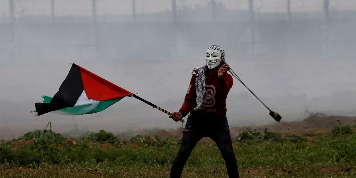 A masked demonstrator holding a Palestinian flag uses a sling to hurl stones at Israeli forces during a protest marking Land Day and the first anniversary of a surge of border protests, at the Israel-Gaza border fence east of Gaza City March 30, 2019. REUTERS/Mohammed Salem