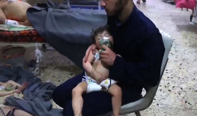 An image grab taken from a video released by the Syrian civil defence in Douma shows an unidentified volunteer holding an oxygen mask over a child's face at a hospital following a reported chemical attack on the rebel-held town on April 8,2018 AFP