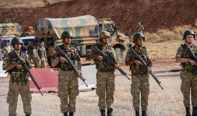 Turkish soldiers stand near armored vehicles near the Turkey-Syria border in this file photo. (AFP)