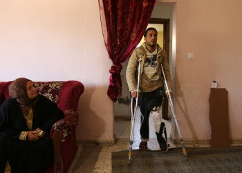 Palestinian man Tamer Abu Daqqa, who said that he was the man whose shooting by an Israeli sniper was captured on a leaked video, walks with crutches inside his home in Khan Younis in the southern Gaza Strip April 11, 2018. REUTERS/Ibraheem Abu Mustafa