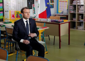 French President Emmanuel Macron arrives inside a classroom prior to attend an one-hour interview with French news channel TF1, at a school in Berd'huis, France, April 12, 2018. Yoan Valat/Pool via Reuters