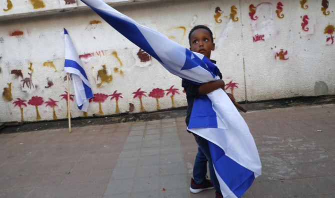 A boy holds the Israeli flag as African migrants and Israelis demonstate in Tel Aviv against the Israeli government's policy to forcibly deport African refugees and asylum seekers /AFP