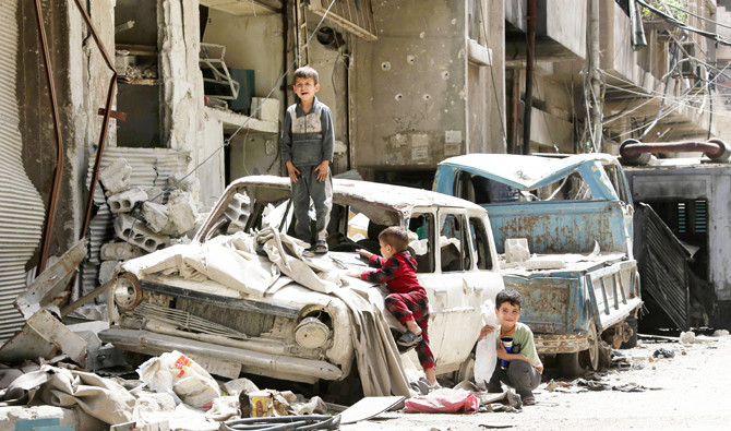 Syrian boys play on a destroyed car in the former rebel-held Syrian town of Douma on the outskirts of Damascus on April 19, 2018, five days after the Syrian army declared that all anti-regime forces have left Eastern Ghouta, following a blistering two month offensive on the rebel enclave. The regime in February launched a blistering assault on Eastern Ghouta, a semi-rural area within mortar range of central Damascus that had been in opposition hands for six years. / AFP / STRINGER