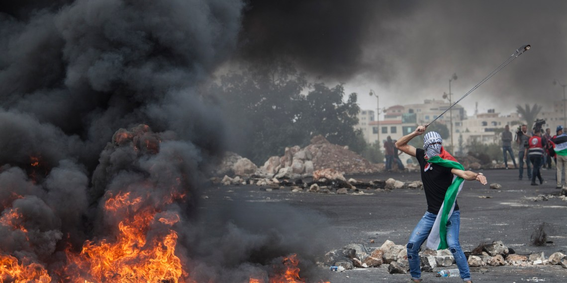A Palestinian protester throwing a rock during a protest against U.S. embassy move to Jerusalem and ahead of the 70th anniversary of NAKBA, at the check point of Bet-Eill, North of Ramallah May 15, 2018. / MEA/ Javier Carbajal