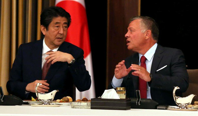 Japan's Prime Minister Shinzo Abe (L) talks with Jordanian King Abdullah II over lunch at the Royal Palace in Amman on May 1, 2018. (AFP/Khalil Mazraawi)