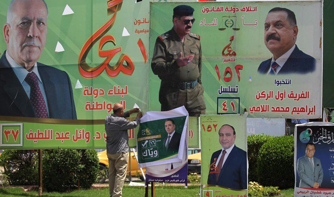 A man hangs an electoral campaign poster in Baghdad ahead of the upcoming parliamentary elections on May 12. Shiite religious parties have come to play a greater role in the years since the 2003 US-led invasion that toppled dictator Saddam Hussein. (AFP)