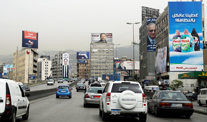 Cars drive past electoral campaign posters on a highway on the northern outskirts of Beirut on May 4, 2018, as Lebanon gets ready for electing its parliament for the first time in nine years this weekend, with its ruling parties seeking to preserve a fragile power-sharing arrangement despite regional tensions.  / AFP / JOSEPH EID