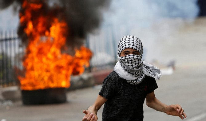 Israeli solider Elor Azaria was initially sentenced to 18 months in prison for the 2016 killing of Abdul Fatah Al-Sharif in the occupied West Bank city of Hebron. Above, a Palestinian protester is seen in front of a burning tire during clashes with Israeli troops in Hebron on May 4. (Reuters)