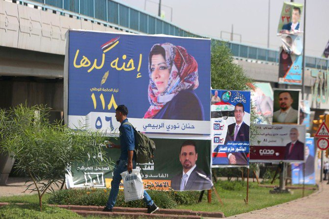 """A man walks past electoral campaign posters in Baghdad on May 8, 2018. Arabic slogan on Hanan Nouri al-Rubaye's billboard (C) reads: """"We are up to it"""". With campaign posters cluttering the streets of Iraq, the almost 7,000 candidates running for parliament in upcoming elections are resorting to increasingly wacky pitches to woo voters. / AFP / SABAH ARAR"""