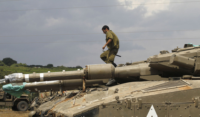 """An Israeli soldier stands on top of Merkava Mark IV tanks as troops take position near the Syrian border in the Israeli-annexed Golan Heights on May 9, 2018. The Israeli-occupied section of the Golan Heights was placed on high alert due to """"irregular activity by Iranian forces"""" across the demarcation line in Syria. / AFP / JALAA MAREY"""