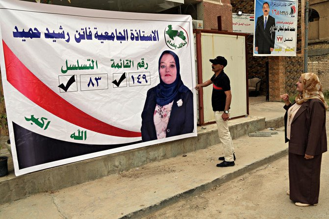 Ahmed Rashid places a campaign posters for his sister, Faten Rashid, a candidate for parliament, in Baghdad, Iraq. (AP)