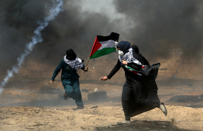Female demonstrators run for cover from tear gas fired by Israeli forces during a protest where Palestinians demand the right to return to their homeland, at the Israel-Gaza border in the southern Gaza Strip. (Reuters)