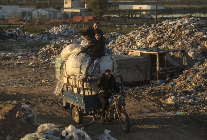 This file image shows Palestinian men on the back of a motor-cart after collecting plastic at a garbage dump (Mahmud Hams/AFP)