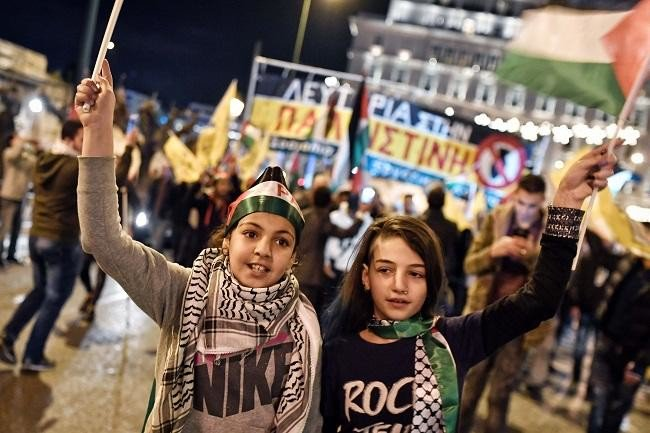 Palestinians children shout slogans and wave flags in a demonstration in Greece. (AFP)
