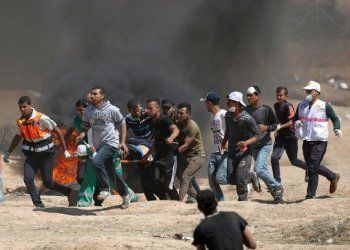 Palestinians carry a demonstrator injured during clashes with Israeli forces near the border between the Gaza strip and Israel east of Gaza City. (AFP)