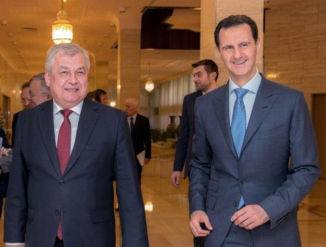Syrian President Bashar Assad (R) welcomes the Russian President's Special Envoy on Syria Alexander Lavrentiev to Damascus. (AFP)
