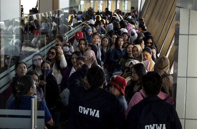 Overseas Workers Welfare Administration officials welcome Filipina workers returning home from Kuwait on February 18. Hundreds of Filipino workers returned to the Philippines from the Gulf nation with horror stories of abuse and hardship. (AFP)