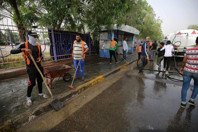 Iraqi municipal workers clean the site of an overnight suicide bomb attack in Baghdad's Shiite suburb of Al-Shoala on May 24, 2018. (AFP/AHMAD AL-RUBAYE)