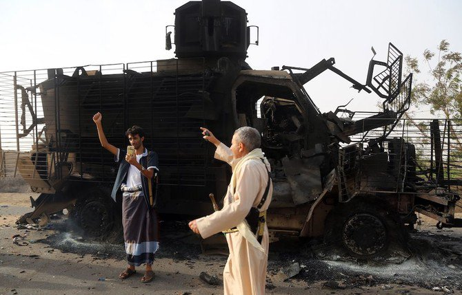 Yemenis check the wreckage of an armoured vehicle after clashes between fighters loyal to exiled President Abedrabbo Mansour Hadi and Houthi rebels. (AFP)