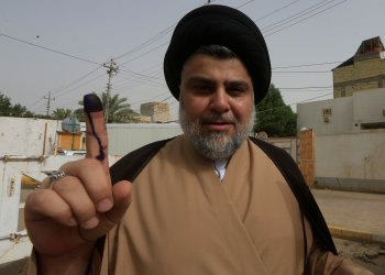 Iraqi Shi'ite cleric Moqtada al-Sadr shows his ink-stained finger after casting his vote at a polling station during the parliamentary election in Najaf, Iraq May 12, 2018. REUTERS/Alaa al-Marjani