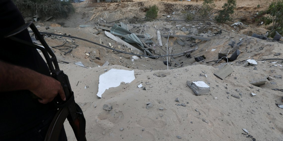 A Palestinian militant stands guard near the destroyed Islamic Jihad military base after it was targeted by an Israeli warplane, the southern Gaza Strip May 30, 2018. REUTERS/Ibraheem Abu Mustafa