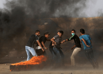 Palestinian demonstrators drag a burning tire during a protest demanding the right to return to their homeland, at the Israel-Gaza border in the southern Gaza Strip May 25, 2018. REUTERS/Ibraheem Abu Mustafa