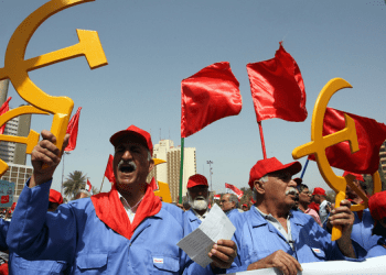 Supporters of the Iraqi Communist Party hold the communist symbol of the hammer and sickle as they wave flags during a march to celebrate International Workers Day in Baghdad (AFP)